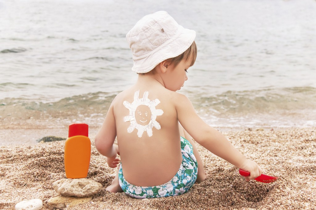 The sun drawing sunscreen (suntan lotion) on baby (boy)  back. Caucasian child is sitting with plastic container of sunscreen and toy on sunny beach. Close up, outdoor (Sharm El Sheikh, Egypt).